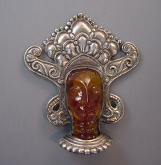 FRED A BLOCK carved apple juice bakelite face fur clip with fabulous headdress, circa 1940.