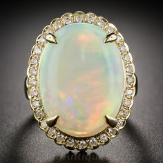 9.77 Carat Opal and Diamond Cluster Ring, USD $3,850. The enchanting gemstone, weighing just shy of 10 carats, is surrounded by half-a-carat carat of sparkling round brilliant-cut diamonds and is crafted in gleaming 18 karat yellow gold. Finger size 7.