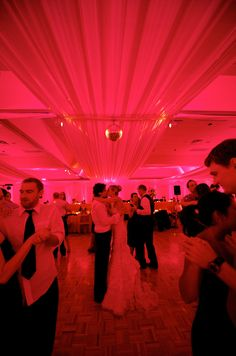 White draping and LED controlled lighting allow you to change the color and feeling of a room instantly. The bride and groom steal a kiss on the dance floor.  Jen Kroll Photography, A Day in May Events. Special Events Rental.