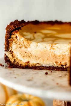 This is the only recipe for Pumpkin Swirled Cheesecake that you'll ever need! The creamiest, most flavorful cheesecake filling and it's paired with a mile-high, thick, buttery gingersnap cookie crust. Click for the recipe or go to just-add-sprinkles.com to get this delicious and dreamy seasonal recipe! #pumpkinswirledcheesecake #cheesecake #easy #best #recipes #fromscratch #pumpkinrecipes #pumpkincheesecake #pumpkindesserts