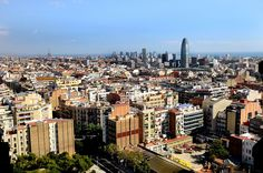 "Barcelona skyline.jpg > Barcelona, Spain, view over the city towards the coast with Torre Agbar, which is illuminate at night in the colours of the ""F. C. Barcelona"""