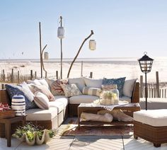 Love this outdoor living space! Cool lanterns hanging from driftwood.#coastalliving