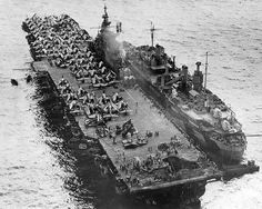 The U.S. Navy aircraft carrier USS Randolph (CV-15) alongside repair ship USS Jason (ARH-1) at Ulithi Atoll, Caroline Islands, 13 March 1945, showing damage to her aft flight deck resulting from a kamikaze hit on 11 March. The photograph was taken from a floatplane from the light cruiser USS Miami (CL-89).