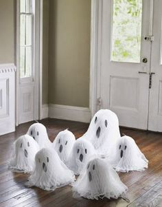 How cute!  White paper wedding bells (can be found at any craft store, stores that sell wedding decorations, and maybe even the dollar store!) white tulle over the bells, and black construction paper cut outs for the ghost face!  Thinking about hanging these on our porch!