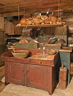 "A ""collected kitchen"" of antique pieces and things made of reclaimed wood, this one is in a replica home in Lancaster, Ohio. Owner Ginny Curry is a master of primitive decorating. She and her husband, Bill, build shelves and cabinets themselves. The room is filled with the owners' collections of wooden bowls, firkins, buckets, baskets, etc. Appliances hide unobtrusively,  making it a modern kitchen in everyday use."