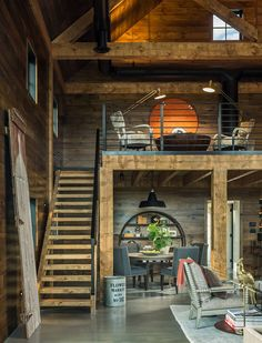 Barn Farmhouse. Rustic barn farmhouse with loft, reclaimed wood shiplap walls, exposed beams, vaulted ceilings, barn lighting and wood and metal stairs. Roundtree Construction. TruexCullins Architecture + Interior Design