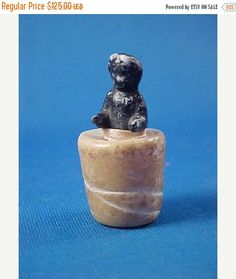 This is a small frozen Charlotte doll encased in wax. The wax is molded in the shape of a thimble so it can be stored inside one. There are