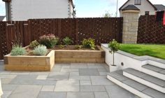 Fairstone black limestone paving and timber sleeper planters