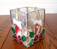 Christmas wouldnt be Christmas without candles. This sparkling stained glass candle holder has all the traditional colors of Christmas. Each of the four sides has a candle, holly and bow. It is equally beautiful on all isdes and would make the perfect centerpiece for your dining room
