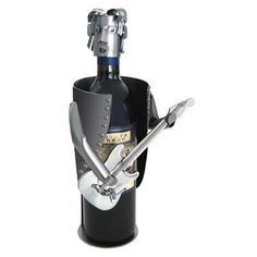 """Guitar Electric Wine Caddy by H & K SCULPTURES. $88.00. 6753 Features: -Wine caddy.-Material: Recycled steel and copper.-Hand crafted.-Great in home or office.-Original art work.-Holds 750 ml bottle. Color/Finish: -Steel and copper finish.-Painted accents. Dimensions: -Overall dimensions: 12"""" H x 4"""" W x 4.5"""" D. Collection: -Wine Caddys collection."""