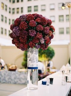 Glass Centerpiece with Burgundy Hydrangeas | Photography: Jose Villa Photography. Read More: http://www.insideweddings.com/weddings/incredible-rooftop-rehearsal-dinner-with-striking-striped-tent/555/