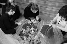 Les petites mains corrigent quelques détails de perlage en backstage du défilé Elie Saab haute couture printemps-été 2014
