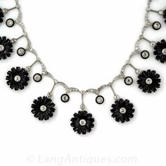 A unique and supremely beautiful late-Edwardian/early-Art Deco necklace in glorious black & white. 15 hand carved, diamond centered onyx flowers alternate with black enamel outlined European-cut diamonds, all of which suspend from a glittering platinum and diamond wing motif links, in this truly singular, sophisticated  and sensational necklace. A ravishing rarity, hand fabricated in platinum, circa 1920s, 18 1/2 inches in length, with original fitted box.