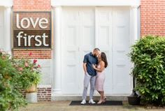 "The ""Love First"" sign outside of the Painted Bride Art Center is a perfect place for engagement photos in Old City Philadelphia. Photo by Nicole Lois Photography"