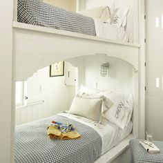 """Great coastal feel to these bunks attained by use of white and blue color, """"crew"""" detail on pillows, mariner style lighting, and bead board."""