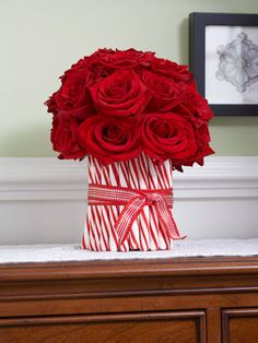 <3 this idea for the holidays! Hot glue peppermint sticks to the outside of a large, square vase. Tie a festive ribbon around the outside and fill with flowers (I love the red roses in this pic!)