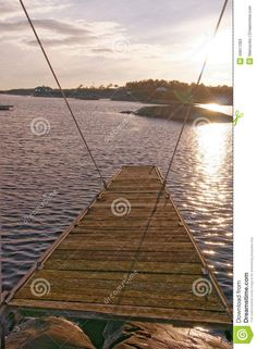 Wooden platform for jumping into the water. Wooden bridge overgrown with moss on the fjord. Sunset over the fjord. Around the winter vegetation and rocks. Vintage look. Winter scenery, snow on the rocks. Kragero, Telemark municipality. Region of southeastern Norway. Skagerrak coast.
