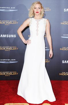 Jennifer Lawrence wears a white Christian Dior Couture dress with embellishment around the shoulder and a scallop neckline