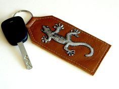"This genuine leather keyring in a tan colour has a cute little pewter repousse Gecko on the front. A lovely gift for a man or a woman     This leather keyring measures 117mm (4 1/2"") (excluding ring) x 50mm ( 2"") wide."