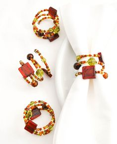 Handmade beaded napkin rings. Set of four (4). Tuscan inspired in shades of deep red, gold, amber, rust, light green and bronze.