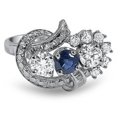 The Bellflower Ring.  A true beauty, this cocktail ring from the Retro era showcases a deep blue sapphire center gem flanked by two sizable diamond accents. Sparkling ribbons of platinum add sparkle and shine to this unique piece