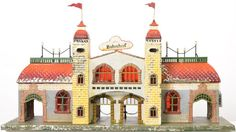 Large Bing tin hand painted train station, very nice but missing paint here and there as seen in the photos, C6. Base measures 23 1/4 x 8 1/4 inches and stands 13 inches tall to the tops of the flags.
