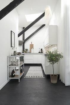 La cuisine sous le toit de cet appartement moderne petit mais très fonctionnel