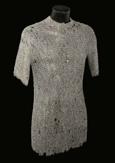 A GERMAN MAIL SHIRT, NUREMBERG   15TH /EARLY 16TH CENTURY   Constructed entirely of rivetted iron rings, with closed front extending over the upper thighs, the back finishing shorter over the base of the thighs, short arms, and the front carrying a brass-headed rivet cast with Nuremberg mark on a raised shield encircled by the inscription 'Nuremberg Statt' in miniscules