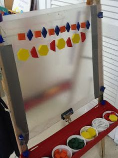 Playfully Learning: Our Sticky Easel . I like the set up of the materials - sorting the pattern blocks into individual cups and the other side has yarn pieces sorted by color. This activity helps children understand patterns and relations and functions Easel Activities, Classroom Activities, Childcare Activities, Kindergarten Classroom, Teaching Math, Teach Preschool, Patterning Kindergarten, Kindergarten Addition, Preschool Shapes