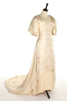 A Liberty & Co ivory satin and silk crêpe bridal gown, circa 1911. with large printed label to the waist stay 'Liberty & Co Ltd, London & Paris', with raised waist-line, the plastron with scrolling Art & Crafts style pearl beaded scrolling carnations, also to under-sleeves and rear back detail, long trained skirt trimmed with ribbons, bust approx 81cm, 32in. Estimate:£350 - £550 - See more at: http://kerrytaylorauctions.com/one-item/?id=76&sub=%20&auctionid=417#sthash.Y7dz6oiV.dpuf