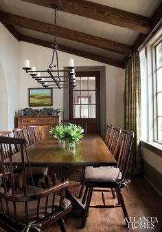 Dining Room: wood beams, white walls, wood floors, wall of windows, small buffet, chandelier, chairs.