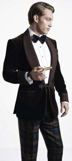 Dark brown cotton silk velvet smoking jacket, black grosgrain bow-tie, green-and-brown checkered pleated trousers, and grosgrain cummerbund; Black lacquer silver tiger decor cufflinks; Emperador timepliece with white-gold case; White cotton shirt.