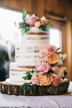 Featured Photographer: Matt McElligott; Lovely three tier rustic wedding cake decorated with orange and pink flowers