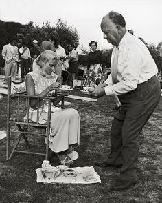 """#1954. Sur le tournage de """"La main au collet"""" le réalisateur Alfred Hitchcock prend soin de sa star Grace Kelly.  Assise sur son fauteuil de cinéma elle se fait servir le thé par le maître du suspense. Photo : Edward Quinn / #ParisMatch by parismatch_vintage"""