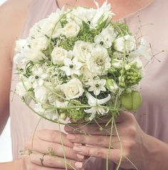 Pretty, feminine white and green dome handtied bridal bouquet with white roses, ornithogalum and trailing vine.