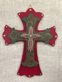 Perfect addition to any home or as a birthday gift or Mothers Day. Larger wooden cross is deep red and measures 12 inches x 9 inches and has a medium green smaller wooden cross on top and a red and gold jeweled cross on top of that. Cross comes with bow in your choice of ribbon color.