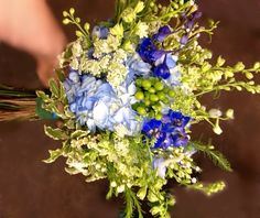 Dill's Floral Haven - Belleville, IL -  www.dillsfloral.com - Designed by Amanda Gain - Alicia Gonzalez and Tony Hamilton Wedding - June 2013 - royal blue delphinium, light blue hydrangeas, white larkspur, Queen Anne's lace, honey bracelet, varigated Italian pittosporum, white waxflower, lime green hypericum berries, light blue delphinium, and rhinestone sprays. A perfect bridal bouquet for a garden or outdoor wedding.