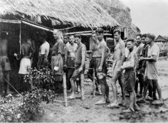 Kanchanaburi, Thailand. January 1945. Kanchanaburi  is fifty kilometres north of Nong Pladuk (also known as Non Pladuk), or 364 kilometres south of Thanbyuzayat. Prisoners of war line up in a meal queue at an attap canteen hut in the POW camp (commonly called Kanburi by the Australians). Many prisoners were brought here from Burma by the Japanese after the Burma-Thailand railway was completed. Note that most prisoners wear rubber clogs on their feet. Most clothing has been lost or worn out.