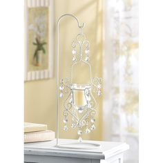 Recreate the romantic mood of a 19th century Parisian apartment with this stunning lighting piece! Meticulous metal scrollwork frame in rich ivory tones perfectly captures the essence of continental living. Delicate dangling beads reflect the candle's glow to create the ideal serene setting for any space. 5 1/2 x 6 3/8 x 16 1/2 high. Iron with glass cup and plastic beads.