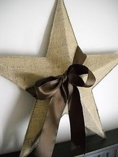 Mod podge a piece of burlap on a rusty thrift store star, trim it with twine and a glue gun, and wrap a brown satin ribbon around it.