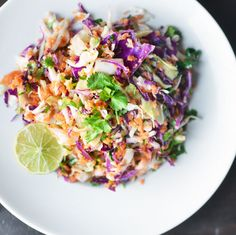 #paleo Slaw + lime dressing: 1/2 head green cabbage, cored; 1/2 head red cabbage, cored; 1 pound carrots, peeled and shredded; 1 large bunch cilantro, leaves roughly chopped; 3 limes, juiced (about 1/3 cup); 2/3 cup neutral oil, such as grapeseed or sesame; 1 to 2 teaspoon honey; Kosher salt and freshly ground pepper