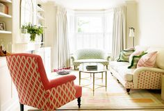 Neutral living room with red patterned chair and lots of natural light