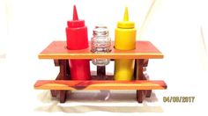 Ketchup and Mustard dispenser is plastic. Wooden picnic table varnish is faded. Salt and Pepper Shaker is glass with metal caps. Comes with Ketchup/Mustard/Salt/Pepper. Salt And Pepper Holder, Wooden Picnic Tables, Condiment Caddy, Vintage Names, Diy Garden Projects, Wood Construction, Ketchup, Wood Crafts, Solid Wood