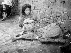 Szydlowiec, Poland, A young Jewish woman nursing a baby in a ghetto street.