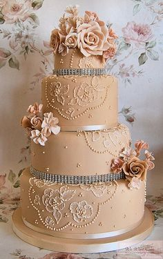 Vintage beauty...tone-on-tone delicate sugar flowers, brush embroidery lace, and dazzling diamond trim accent this antiqued ecru wedding cake to perfection. Created by talented cake artist Emma Procopiou, proprietor of We Want Cake in Cheshunt, Hertfordshire, England....