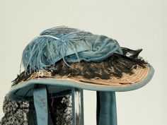 Ca.1865 hat of .5cm wide straw plait handstitched in a spiral from center of crown. Brim faced w/ turquoise-blue ribbed silk, w/ separate head and side lining. Wired at edge of brim. Trimmed with twisted blue velvet ribbon and ribbed silk ribbon. Frill over brim of black machine lace and cream silk lace. Single blue ostrich feather over crown and a blue ribbon bow and streamer with a wide streamer of black lace. Snowshill Wade Costume Collection (National Trust).