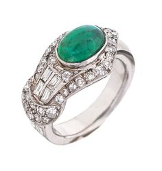 An emerald diamond ring C. 1940. 18 ct. white gold, marked. In front one oval emerald cabochon c. 1,50 ct. (8,2 x 6 mm), framed by 6 diam. in baguette cut and 34 small diam. in 8/8 cut in total c. 0,90 ct. I-J.vsi-P. In front w. 12 mm