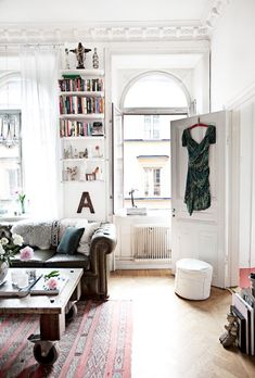 Bright white eclectic boho living room with crown moulding and an old rug. leather couch. What my pied-a-terre in Paris will be