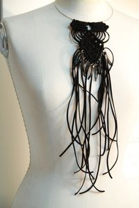A unique macrame necklace with black cord , and black fresh shells claws.