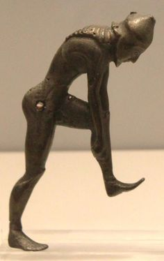A Spartan Prepares for War. A foot-soldier puts a greave on the left leg.  Handle of a Laconian krater (vase for mixing wine with water), 555-540 BC  From Tsotyli near Kozani in Macedonia  Athens, National Archaeological Museum, Bronze Collection
